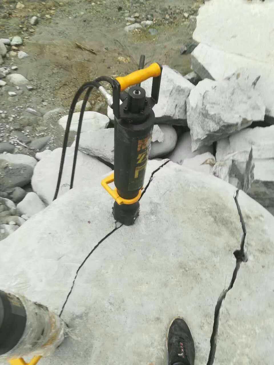 愚公斧新型岩石劈裂机首先,在被分裂的物体上钻一些特定直径和深度的孔,将分裂机的楔块组插入钻好的孔中。液压动力站产生高压液压油,通过分裂机上的液压缸,驱动楔块组中的中间楔块向前驶出,并将两个反向楔块向两边撑开。从而产生巨大分裂力将被分裂的物体结构内部破坏掉,数秒钟内被分裂的物体就会产生10 - 40毫米的裂纹并被分裂开来。